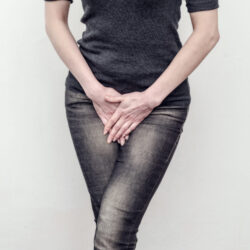 Woman with urinary incontinence standing with legs crossed trying to hold in urine | CU Medicine OB-GYN East Denver (Rocky Mountain) | Denver CO