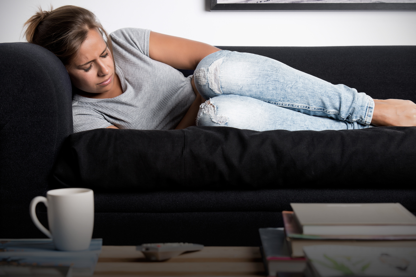 fibroids | CU Medicine OB-GYN East Denver (Rocky Mountain) | woman in pain on couch